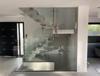 Garde corps en verre sur rail et pince sur un escalier design
