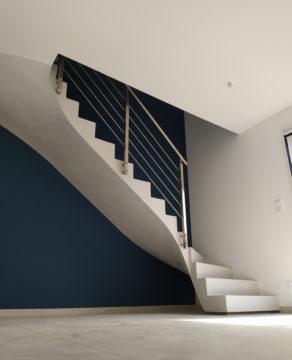 Garde corps en inox brossé sur un escalier en béton ciré blanc