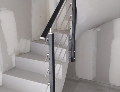 Garde corps en inox sur un escalier à paillasse décoré en béton ciré